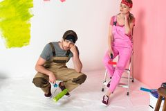 tired young couple in working overalls sitting with paint royalty free stock photo