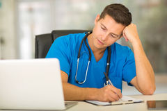 Tired young doctor working Stock Photography