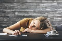 Stress, boredom concept. Tired young european woman sleeping on wooden office desk with coffee cup and supplies. Stress, boredom concept Stock Images