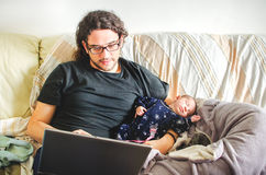 Tired young father take care of baby while trying to work at not Royalty Free Stock Photos