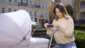 Tired young female falling asleep while swinging newborn carriage, lack energy. Stock footage stock footage
