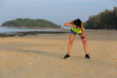 Fitness woman runner have a rest on beach. Tired young fitness woman runner have a rest on beach Stock Photo