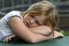 Tired young girl. Tired young 8 year old girl outside resting her head in her arms Stock Photo