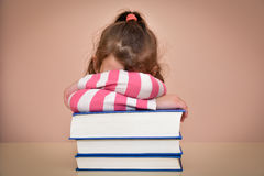 Tired young girl and books Stock Photo