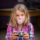 Tired young girl with bubblegum and camera Royalty Free Stock Image
