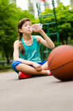 Tired young girl drinking water Stock Photography