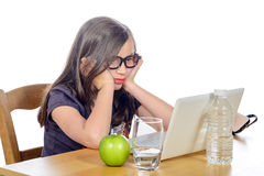 Tired young girl in front of her laptop Stock Image