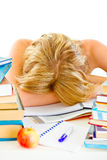 Tired young girl sleeping at table with books Stock Photo