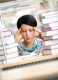 Tired young girl surrounded with books. Tired young girl with headache sitting at the desk surrounded with piles of books Royalty Free Stock Photo