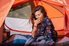 Tired young girl yawning at tent inside. Tired young woman yawning at red tent inside royalty free stock photography