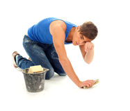 Tired young man cleaning floor Stock Images