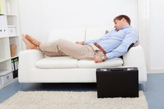 Tired Young Man On Couch Royalty Free Stock Photography