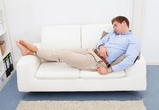 Tired young man on couch Stock Photo
