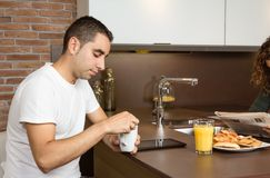 Tired young man with cup of coffee in a breakfast Stock Image