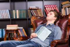 Tired young man dozing off in the library Stock Image