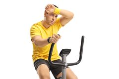 Tired young man exercising on a cross-trainer machine Royalty Free Stock Images