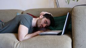 Tired Young Man Falling Asleep on Laptop Computer. Close Up of Tired Young Man with Dark Hair Falling Asleep while Working Laptop Computer on a Couch stock photos