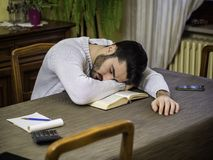 Tired young man falling asleep reading book. Over-worked, tired young man at home sleeping instead of working or studying, resting head over book. Tired male stock photography