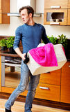 Tired young man with laundry basket Royalty Free Stock Photos