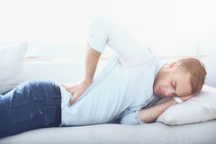 Tired young man laying in the sofa with backache. Stressful pain. Handsome sad young man closing eyes and touching his back while laying in the sofa Royalty Free Stock Image