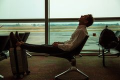 Tired young man lit on seat in airport hall. Guy sleeps. He lean on suitcase. royalty free stock images