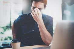 Tired young man making pause after hard work day.Coworker working process at sunny office.Horizontal.Blurred background. royalty free stock image