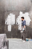 Tired young man with paint roller renovating home stock images