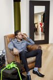 Tired young man sitting on armchair in fashion store Stock Images