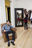 Tired young man sitting on armchair while woman looking at herself in mirror Royalty Free Stock Photography