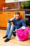 Tired young man sitting on the floor with laundry basket Royalty Free Stock Photos