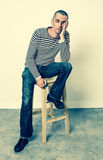 Tired young man sitting, leaning face on hand to nap Royalty Free Stock Photography