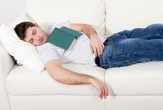 Tired young man sleeping on couch with book on lap Royalty Free Stock Photo