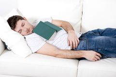 Tired young man sleeping on couch with book on lap Stock Photography