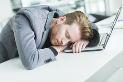 Tired young man sleeping in the office. Tired young man sleeping at the desk in the office Stock Photos
