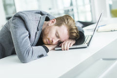 Tired young man sleeping in the office. Tired young man sleeping on the desk in the office Stock Photography