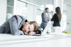 Tired young man sleeping in the office. Young men sleeping in the office Royalty Free Stock Photo