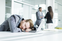 Tired young man sleeping in the office. Tired young men sleeping at the desk in the office Royalty Free Stock Image