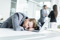 Tired young man sleeping in the office. Tired young men sleeping on the desk in the office Royalty Free Stock Images