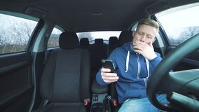 Tired young man smoking and using smartphone in the car in 4K stock video