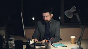 Tired young man in suit and tie is working on computer in office at night sitting at desk in dark room, looking at stock video