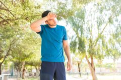 Tired Man Wiping His Forehead After Jogging In Park. Tired young man wiping his forehead after jogging in park on sunny day Stock Image