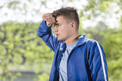 Tired young man wiping sweat after jogging at park Stock Images
