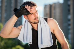 Tired young man wiping sweat off of his forehead after a hard workout stock photography