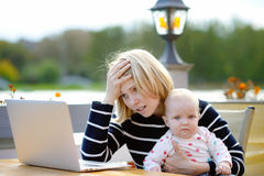 Tired young mother working oh her laptop Royalty Free Stock Photos