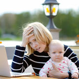 Tired young mother working oh her laptop Royalty Free Stock Photo