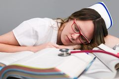 Tired Young nurse with cap, sleeping. Young sleeping female nurse student  wearing white scrubs, laying on school books with stethoscope Royalty Free Stock Photo