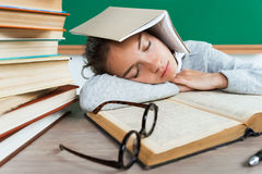 Tired young pupil fell asleep among books. Stock Photography
