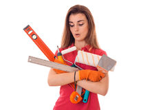 Tired young slim builder girl makes renovations with tools in her hands isolated on white background Royalty Free Stock Image