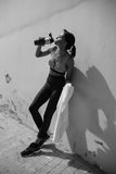Tired young sportswoman leaning on wall at stadium and drinking water from sports bottle. Black and white photo Stock Image