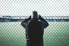 Tired young sporty man leaned and holding on to the rabitz fence. Runner resting near the fence. Concept royalty free stock photos